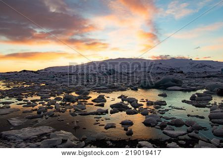 The Glacier Lagoon on the south coast of Iceland (Jokulsarlon) contains thousands of icebergs from the nearby Breidamerkurjokull Glacier. Its still waters reflect the brilliant light of a sunset.