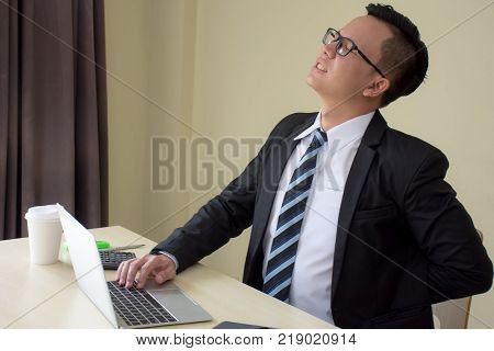Asian businessmen in a suit working hard and feeling painful touching back with pained expressionat after long working hours,Healthy/Office syndrome concept.