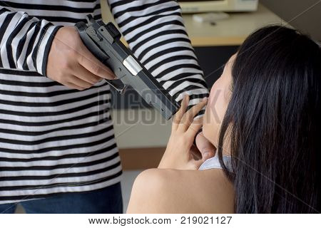 Portrait of Asian scared girl Hostage of terrorist or burglar threatened by a gun point to woman.Criminal and robbery for woman safety concept.