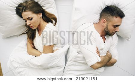Top view of young upset couple lying in bed have problems after quarrel and angry to each other at home