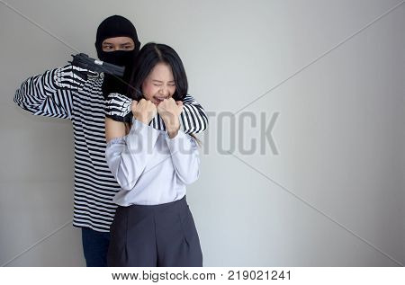 Robbery make a scared young Asian victim to walk alone in a lonely alley/Hostage of terrorist or burglar threatening with gun isolated on a white background, criminal concept