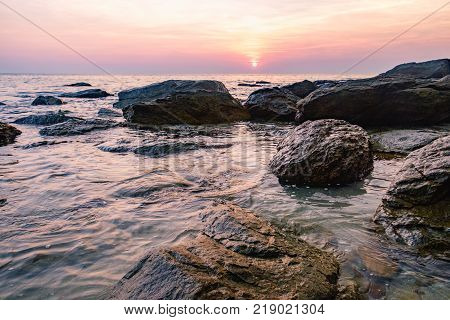 Tropical colourful sunset on the beach of Koh Chang island, Gulf of Siam, Thailand. View of dark night sea with protruding stones.