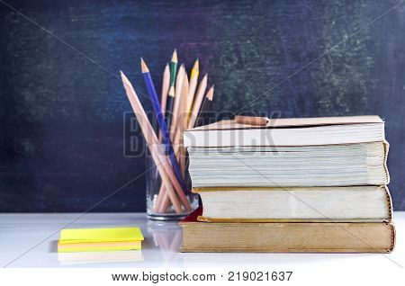 Hardback and textbook stacked with pencils on the table on the blackboard background. The concept of intelligence comes from education. focused on the textbook.