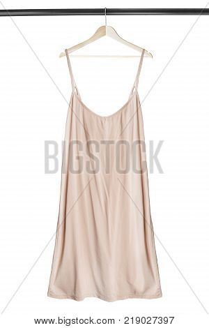 Beige elegant sundress on wooden clothes rack isolated over white