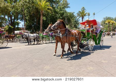 Marrakech Morocco - May 12 2017: Horse drawn carriage taking tourists for a ride on the road leading to Jemaa el-Fnaa square in Marrakech Morocco