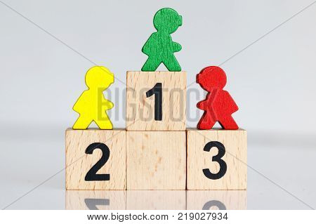 Miniature people: colorful figures standing on wooden podium 123 with business team competition concept.