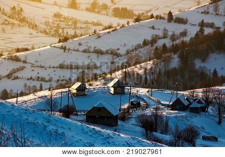 village on a snowy hillside at sunrise. beautiful countryside scenery in winter
