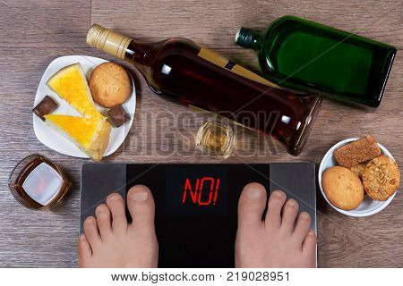Male Feet On Digital Scales And Sign No Surrounded By Bottles And Glasses Of Alcohol, Plates With Sw