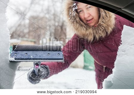 Woman cleans the snow from the car window with a scraper in winter the view from the inside