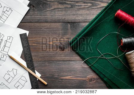Desk of clothing designer. Textile and pattern of clothing on dark wooden background top view.