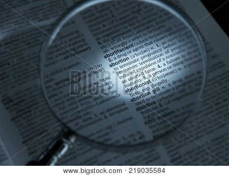 CLECKHEATON, WEST YORKSHIRE, UK: MAGNIFYING GLASS ON DICTIONARY PAGE SHOWING DEFINITION OF THE WORD ABORTION, CIRCA 2005, CLECKHEATON, WEST YORKSHIRE, UK