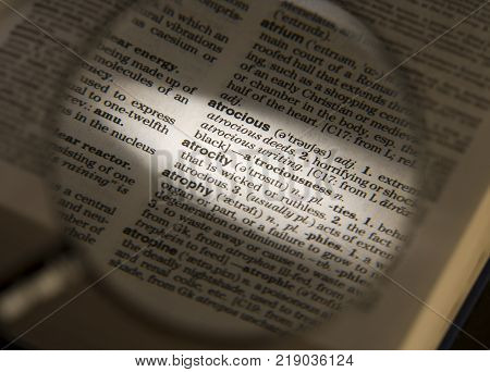 CLECKHEATON, WEST YORKSHIRE, UK: MAGNIFYING GLASS ON DICTIONARY PAGE SHOWING DEFINITION OF THE WORD ATROCITY, CIRCA 2006, CLECKHEATON, WEST YORKSHIRE, UK