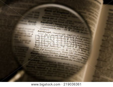 CLECKHEATON, WEST YORKSHIRE, UK:MAGNIFYING GLASS ON DICTIONARY PAGE SHOWING DEFINITION OF THE WORD BANKRUPT, CIRCA 2005, CLECKHEATON, WEST YORKSHIRE, UK