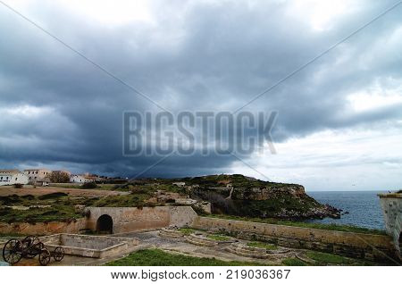 Castle Walls Barracks and Old Gun of La Mola Fortaleza Isabel II in Cloudy Day Outdoors. Menorca Balearic Islands