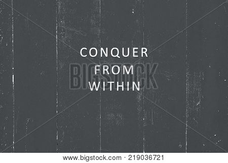 Inspirational quote - Conquer from within. Blurry background.