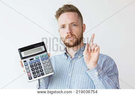 Portrait of attractive serious young man holding calculator and pointing finger up. Broker calling clients for using professional financial service. Finance concept.