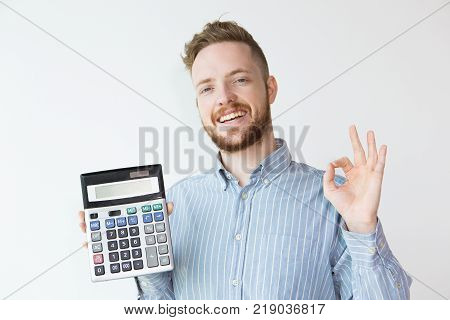 Portrait of attractive content young man with ok gesture holding calculator. Banker offering favorable credit terms. Finance concept.