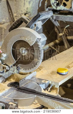 Disc electric circular saw. Sawing machine in a working carpentry workshop. Mechanized woodworking carpenter tool. Miter saw blade.