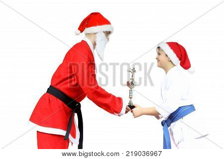 With a black belt Santa Claus hands the athlete with a blue belt sports cup