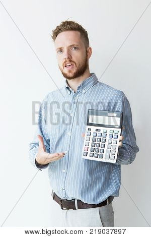 Portrait of irritated young manager holding calculator with presenting gesture. Cheated investor showing loss. Finance or disadvantage concept.
