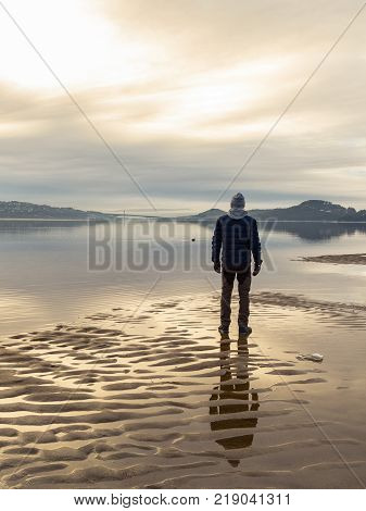 Man standing at the beach in the Norwegian fjord Tovdalsfjorden, looking at the calm sea and the mist and fog. Sand patterns and reflections of the man in the water. Hamresanden, Kristiansand, Norway. Vertical image.