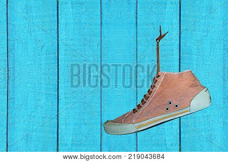 Single Trendy Gym shoe hangs on blue stained wooden wall taken closeup.Empty space for text.