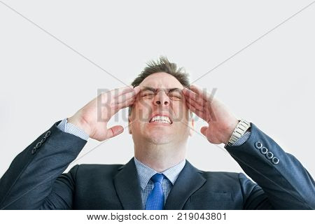 Closeup of stressed middle-aged business man touching temples with his eyes closed tight. Isolated front view on white background. Overwork concept.