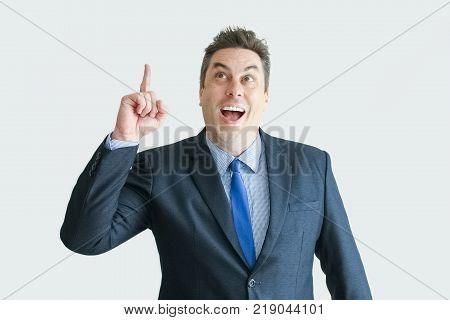 Closeup portrait of joyful middle-aged business man pointing finger upwards. Isolated front view on white background. New idea concept.