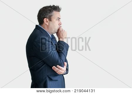 Closeup of smiling middle-aged business man touching mouth and thinking. Isolated side view on white background. Contemplation concept.