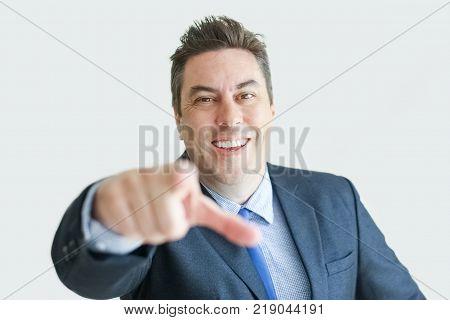 Closeup of smiling middle-aged business man looking at camera and pointing finger at viewer. Isolated front view on white background. Choice concept.