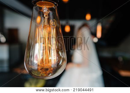 stylish groom and happy bride kissing under retro bulbs lights in wooden barn. rustic wedding concept, space for text. newlyweds couple embracing, sensual romantic moment