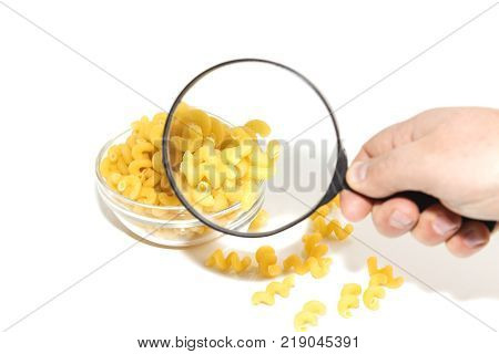 Dried raw, uncooked spirelli pasta noodles backlit in glass container isolated on white background, under a microscope, magnifying glass, space for text.
