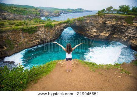 Young woman in Broken beach is beautiful rock coastline in Nusa Penida island nex to Bali, Indonesia