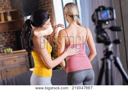 Massage technique. Positive nice young woman standing in front of her friend and looking at her back while presenting massage techniques