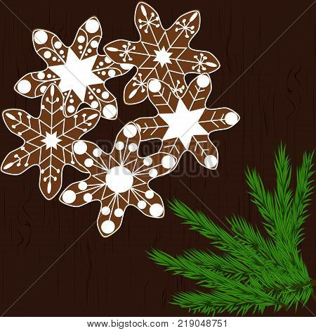 Christmas cookies in the form of snowflakes on a dark wooden background with branches of a Christmas tree