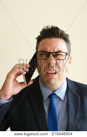 Unhappy frowning businessman looking with disgust while talking to unpleasant client on phone. Sullen emotional sales manager using mobile phone. Work with customer concept
