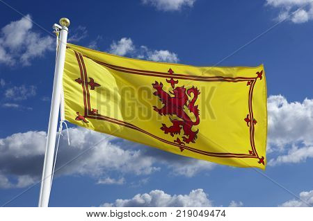 SCOTTISH YELLOW AND RED NATIONAL FLAG WITH BLUE SKY AND WHITE CLOUDS