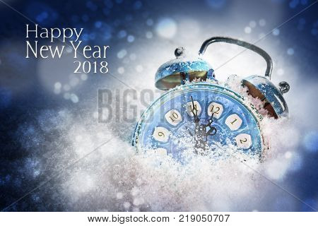 new year 2018 concept blue vintage alarm clock in the snow shows five minutes before twelve dark background with bokeh lights text