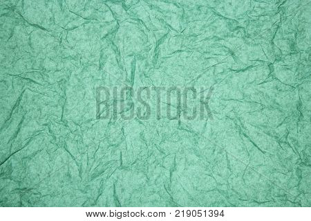ABSTRACT RANDOM BACKGROUND OF CREASED CRUMPLED TURQUOISE TISSUE PAPER