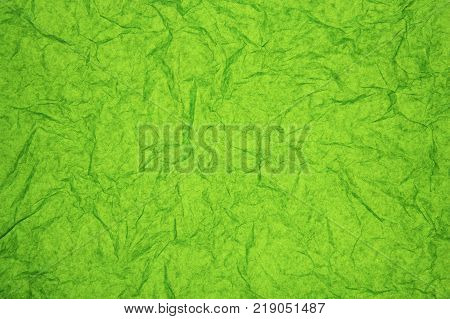 ABSTRACT RANDOM BACKGROUND OF CREASED CRUMPLED PALE GREEN TISSUE PAPER