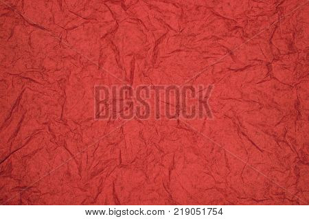 ABSTRACT RANDOM BACKGROUND OF CREASED CRUMPLED RED TISSUE PAPER