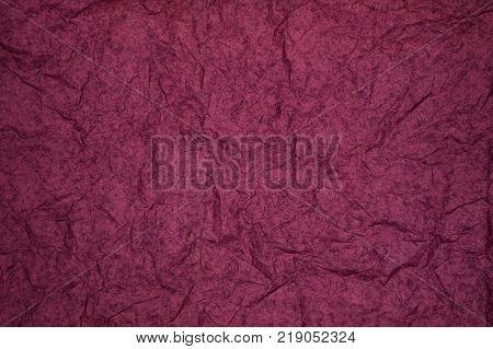 ABSTRACT RANDOM BACKGROUND OF CREASED CRUMPLED DARK PURPLE TISSUE PAPER