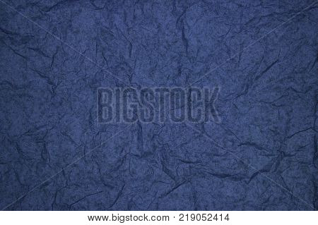 ABSTRACT RANDOM BACKGROUND OF CREASED CRUMPLED NAVY TISSUE PAPER