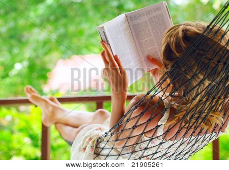 Young woman lying in hammock in a garden and reading a book. Shallow DOF. Focus on a left shoulder