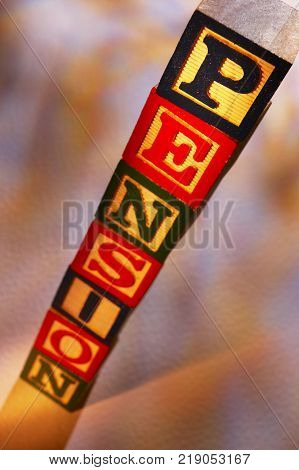 STACK OF WOODEN TOY BUILDING BLOCKS SPELLING THE WORD PENSION