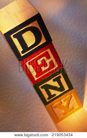 STACK OF WOODEN TOY BUILDING BLOCKS SPELLING THE WORD DENY