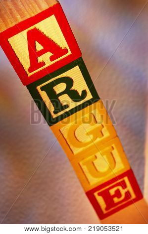 STACK OF WOODEN TOY BUILDING BLOCKS SPELLING THE WORD ARGUE
