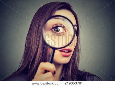 Curious woman looking through a magnifying glass