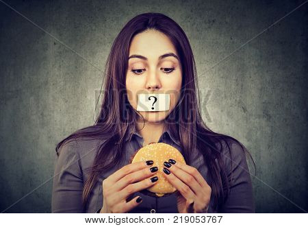 Woman on diet restriction with question mark on her mouth looking at tasty burger isolated on gray background