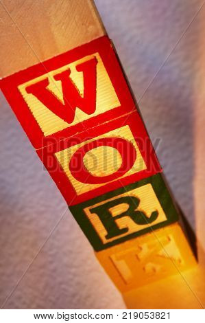 STACK OF WOODEN TOY BUILDING BLOCKS SPELLING THE WORD WORK